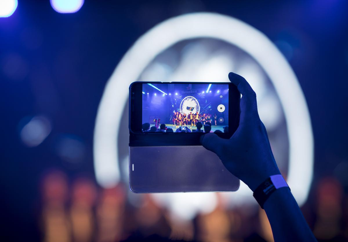 A man takes a photograph of a musical performance on a smartphone during the UEFA Champions League Trophy Tour presented by Heineken on April 4, 2018 in Phnom Penh, Cambodia.