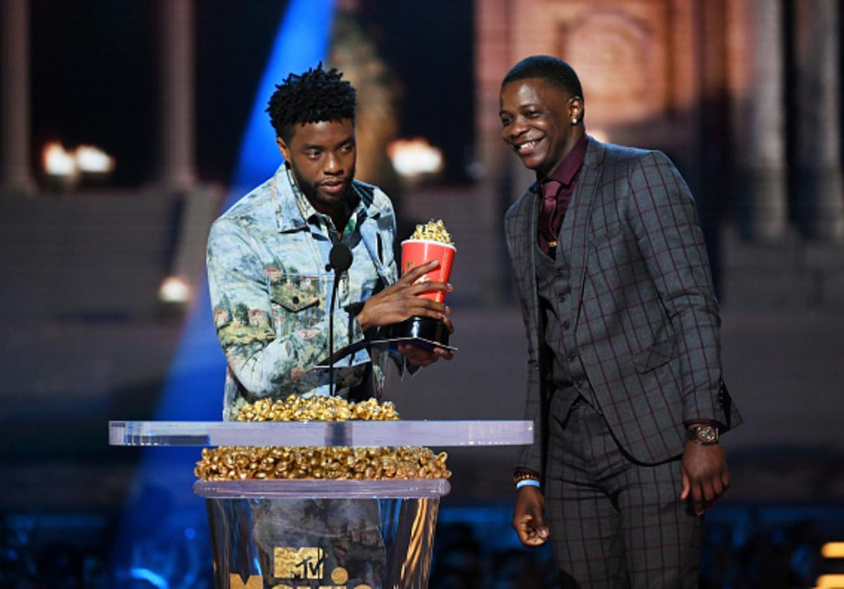 Actor Chadwick Boseman (L), winner of the Best Hero award for 'Black Panther,' presents his trophy to James Shaw Jr. onstage during the 2018 MTV Movie And TV Awards at Barker Hangar on June 16, 2018 in Santa Monica, California.