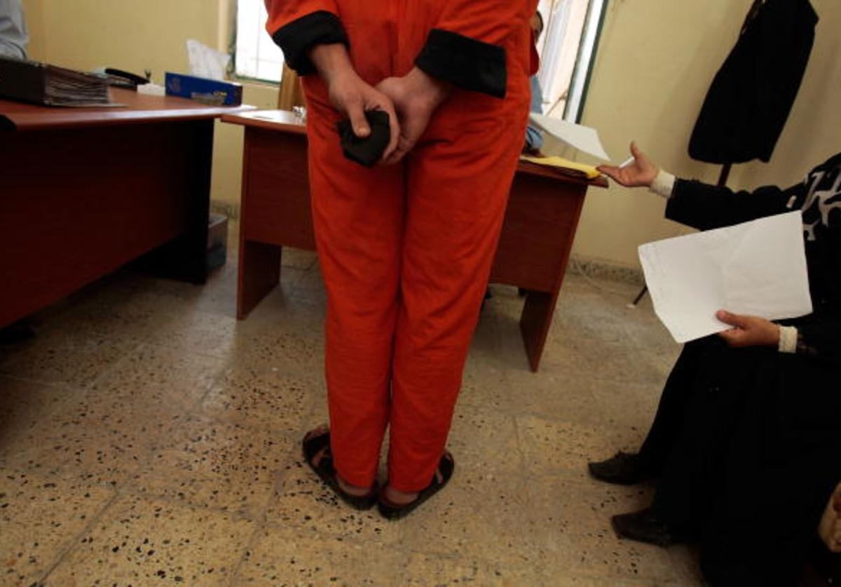 An arrested Iraqi man who's been chosen to appear before Iraqi judges stands in a makeshift courtroom while his court appointed lawyer (R) hands paperwork to the judge November 6, 2007 in Baghdad, Iraq.