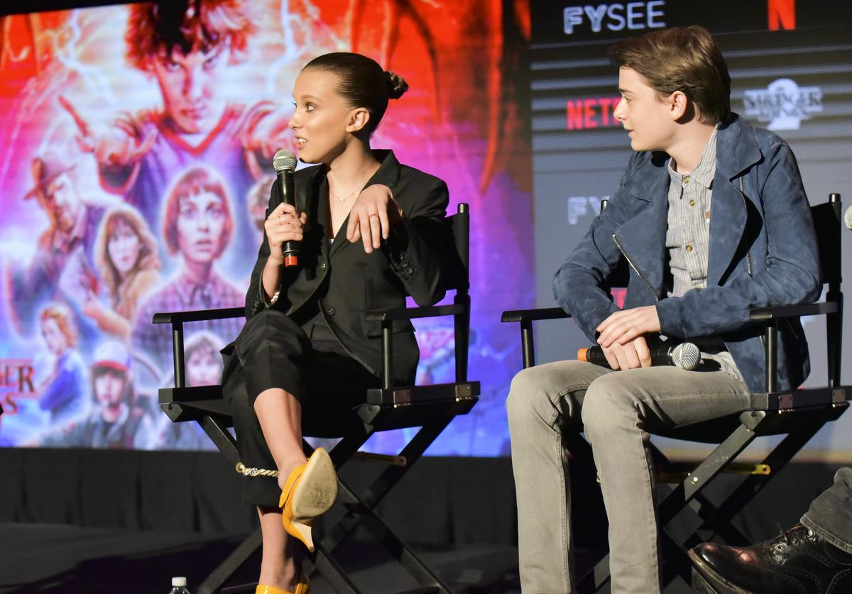 : Millie Bobby Brown (L) and Noah Schnapp speak on stage at #NETFLIXFYSEE event for 'Stranger Things' at Netflix FYSEE at Raleigh Studios on May 19, 2018 in Los Angeles, California.