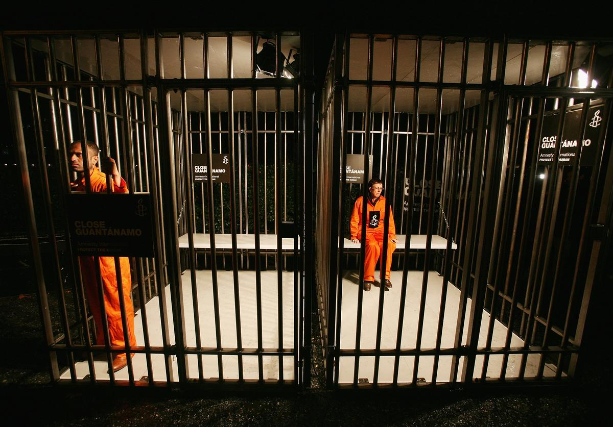 Amnesty International supporters wearing orange boiler suits hold a night long vigil in a cage outside of the US embassy on January 10, 2008 in London, England.