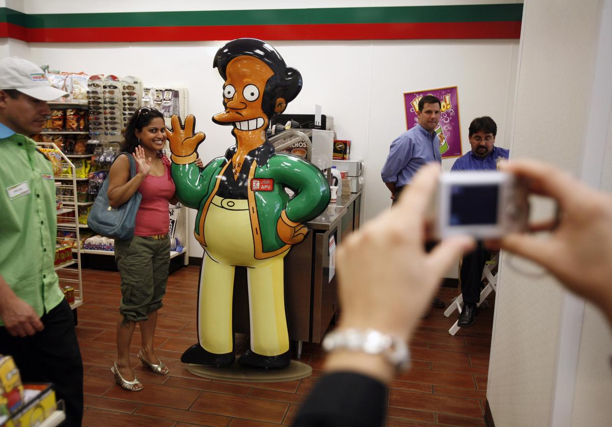 Shelly Ramsammy poses with a representation of 'Apu,' fictional owner of the Kwik-E-Mart from the long-running televsion cartoon show 'The Simpsons' at the 7-11 store at 345 W 42nd Street, converted to a Kwik-E-Mart to promote 'The Simpsons Movie' opening next month, July 2, 2007 in New York City.