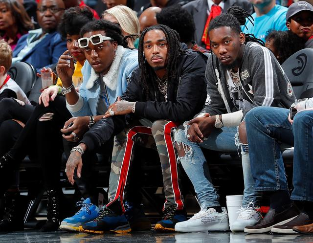 Migos sitting courtside at a basketball game