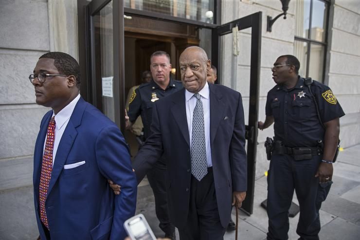 Bill Cosby, center, leaves the Montgomery County Courthouse, led by Andrew Wyatt, left, and behind his new legal team, after details of the new trial were decided by the court August 22, 2017 in Norristown, Pennsylvania. Bill Cosby and his new lawyers will have a hearing in Montgomery County Court about dropping his old counsel, adding his new counsel and if the jury pool will be taken out of county again.
