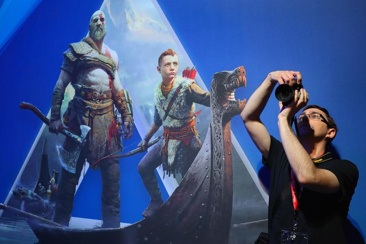 An attendee takes a photograph near an ad for 'God of War 4' during the Electronic Entertainment Expo E3 at the Los Angeles Convention Center on June 13, 2017 in Los Angeles, California.
