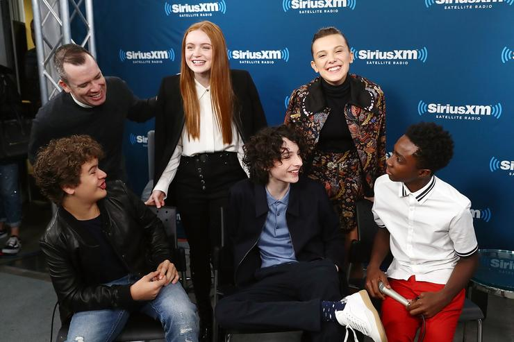 SiriusXM host Tim Stack poses for photos with actors Sadie Sink, Millie Bobby Brown, Caleb McLaughlin, Finn Wolfhard and Gaten Matarazzo during SiriusXM's 'Town Hall' cast of Stranger Things.