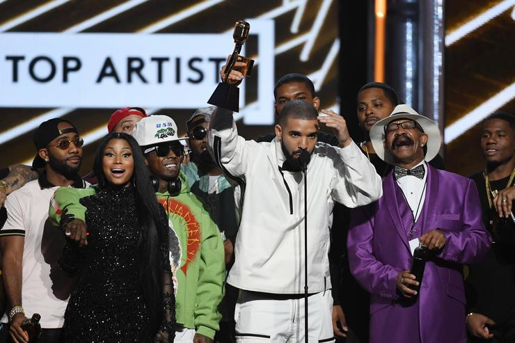 Nicki Minaj and Lil' Wayne look on as recording artist Drake accepts the Top Artist award onstage with his father Dennis Graham during the 2017 Billboard Music Awards at T-Mobile Arena on May 21, 2017 in Las Vegas, Nevada