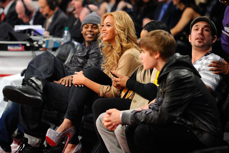 Beyonce Knowles (C) and Justin Bieber (R) sit in the audience during the 2011 NBA All-Star game at Staples Center on February 20, 2011 in Los Angeles, California