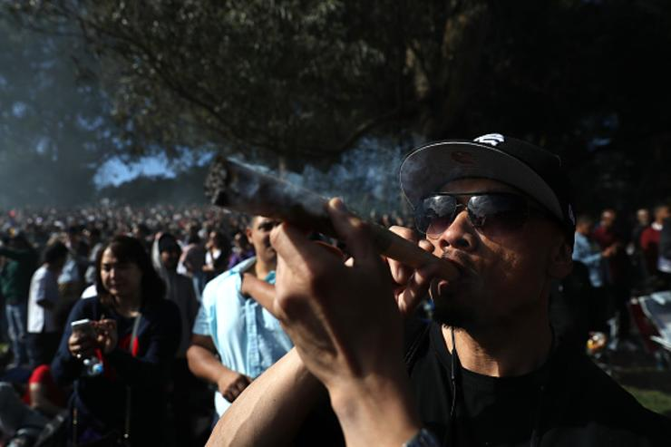 A marijuana user smokes an oversized joint during a 420 Day celebration on 'Hippie Hill' in Golden Gate Park on April 20, 2018 in San Francisco, California.