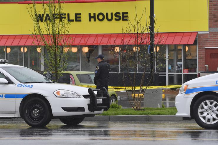 Law enforcement stand outside a Waffle House where four people were killed and two were wounded after a gunman opened fire with an assault weapon on April 22, 2018 in Nashville, Tennessee
