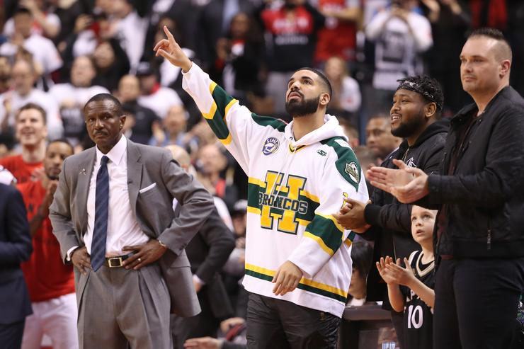 Rap artist Drake celebrates as head coach Dwane Casey of the Toronto Raptors looks on in the closing moments of their victory against the Washington Wizards in the first quarter during Game One of the first round of the 2018 NBA Playoffs at Air Canada Centre on April 14, 2018 in Toronto, Canada.