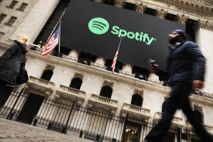 People walk by the New York Stock Exchange (NYSE) on the morning that the music streaming service Spotify begins trading shares at the NYSE on April 3, 2018 in New York City. Trading under the symbol SPOT, the Swedish company's losses grew to 1.235 billion euros ($1.507 billion) last year, its largest ever.