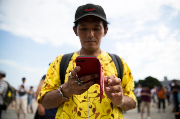 A man plays Nintendo Co.'s Pokemon Go augmented reality game on his smartphone during the Pikachu Outbreak event hosted by The Pokemon Co. on August 9, 2017 in Yokohama, Kanagawa, Japan.