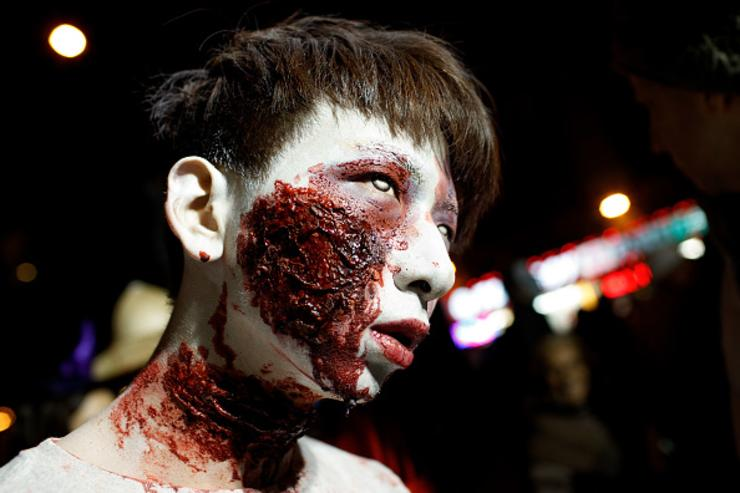 A man dressed as a zombie walks along Sixth Avenue during the 43rd annual Village Halloween Parade, October 31, 2016 in New York City. Thousands of people are expected to attend as the parade travels up Sixth Avenue through the West Village.