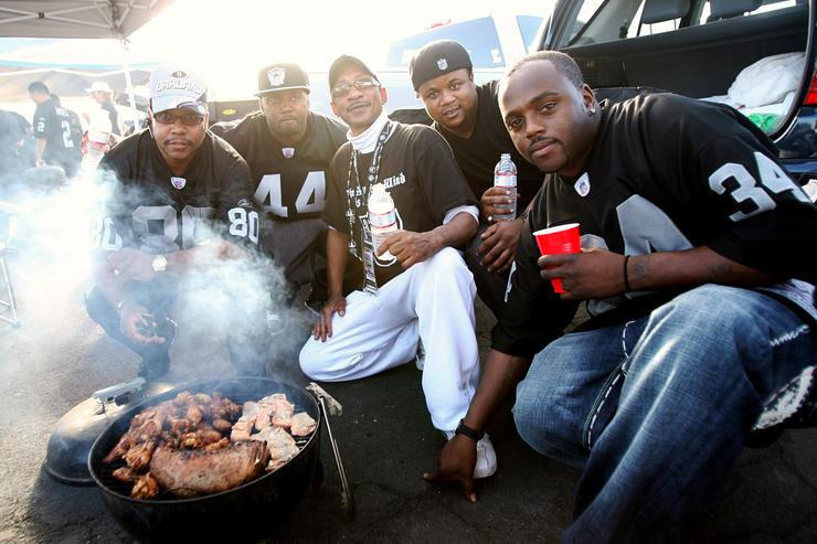 Fans of the Oakland Raiders pose for a photo as they tailgate in the parking lot prior to the Raiders playing against the San Diego Chargers on September 14, 2009 at the Oakland-Alameda County Coliseum in Oakland, California.