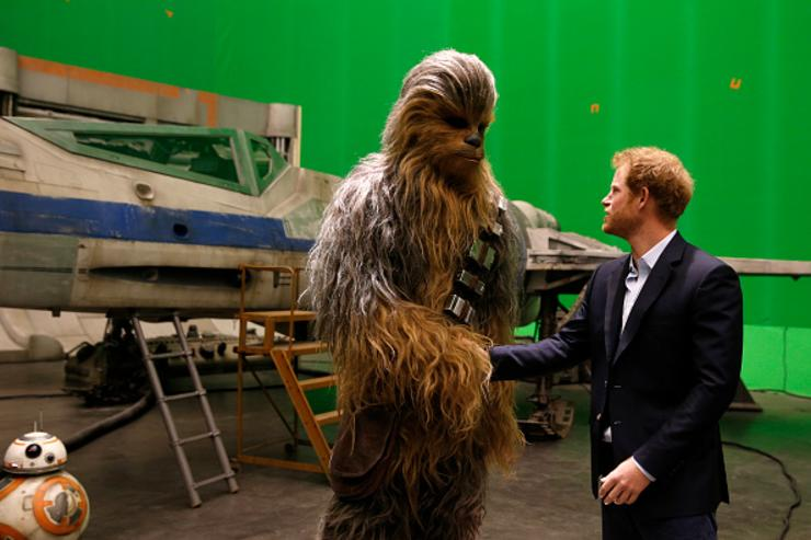 Prince Harry (R) meets Chewbacca during a tour of the Star Wars sets at Pinewood studios on April 19, 2016 in Iver Heath, England.