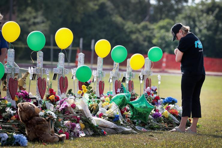 Mourners visit a memorial in front of Santa Fe High School on May 22, 2018 in Santa Fe, Texas. The makeshift memorial honors the victims of last Friday's shooting when 17-year-old student Dimitrios Pagourtzis entered the school with a shotgun and a pistol and opened fire, killing 10 people.