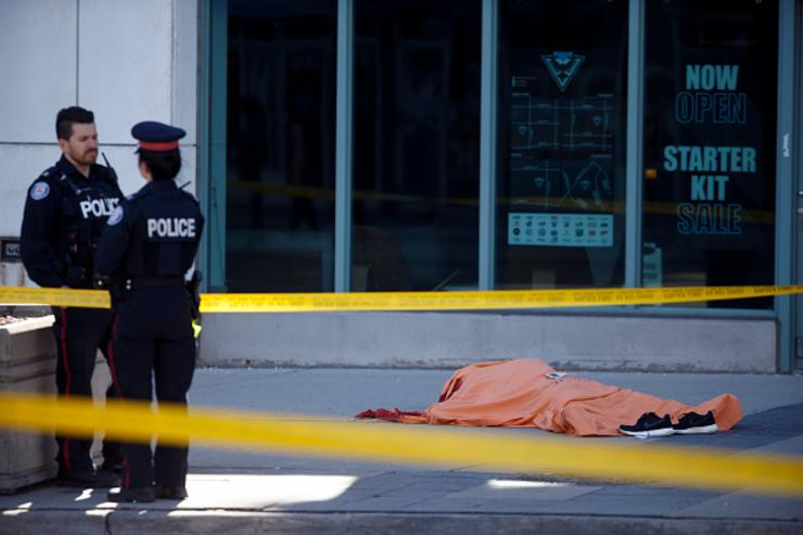 A tarp covers an unidentiified body on Yonge St. at Finch Ave. after a van plowed into pedestrians on April 23, 2018 in Toronto, Ontario, Canada. A suspect is in custody after a white van collided with multiple pedestrians killing nine and injuring at least 16.