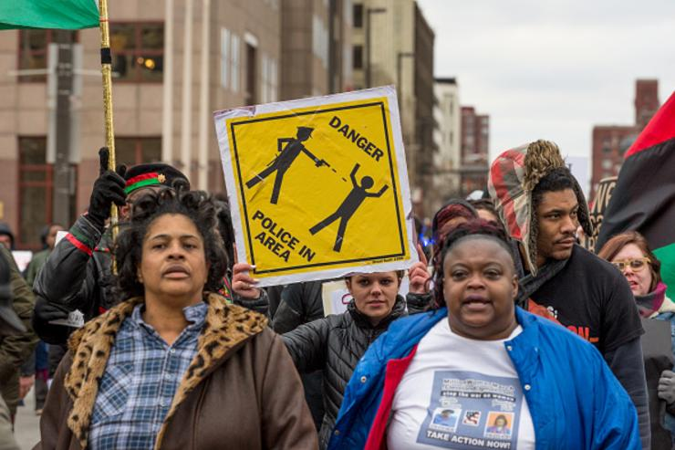 Katy Kostenko (Holding sign), a 19-year old resident of Cleveland, marches with other activists on St Clair Ave. on December 29, 2015 in Cleveland, Ohio.