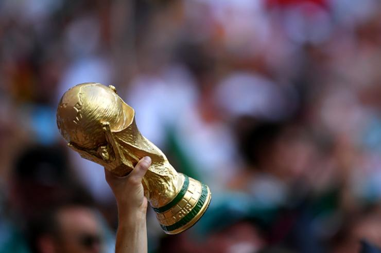 A fan holds up a replica World Cup trophy as he enjoys the pre match atmosphere prior to the 2018 FIFA World Cup Russia group F match between Germany and Mexico at Luzhniki Stadium on June 17, 2018 in Moscow, Russia.