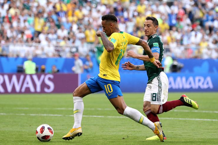 Neymar Jr of Brazil gets away from Andres Guardado of Mexico on his way to setting up Brazil's second goal during the 2018 FIFA World Cup Russia Round of 16 match between Brazil and Mexico at Samara Arena on July 2, 2018 in Samara, Russia
