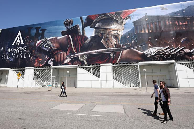 Game enthusiasts and industry personnel walk past a 'Assassin's Creed Odyssey' advertisemtn during the Electronic Entertainment Expo E3 at the Los Angeles Convention Center on June 12, 2018 in Los Angeles, California.
