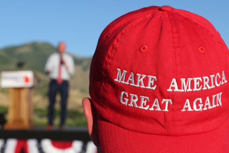 A Romney supporter listens to a speaker as he wears a 'Make America Great Again' hat at the Mitt Romney election party on June 26, 2018 in Orem, Utah. It is primary election day in Utah and Romney is running for the Utah U.S. Senate seat of Senator Orin Hatch who is retiring