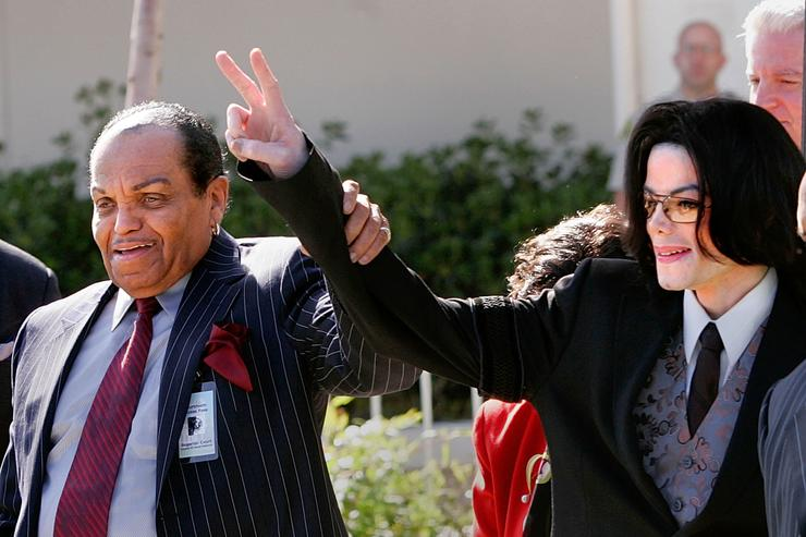 Singer Michael Jackson (R) and his father, Joe Jackson, gesture to supporters following proceedings at the Santa Maria Superior Court during the second week of the trial March 7, 2005 in Santa Maria, California. Michael Jackson is charged in a 10-count indictment with molesting a boy, plying him with liquor and conspiring to commit child abduction, false imprisonment and extortion. He has pleaded innocent.