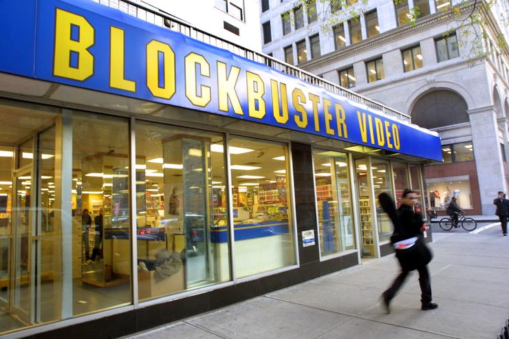 A man walks past a Blockbuster Video store