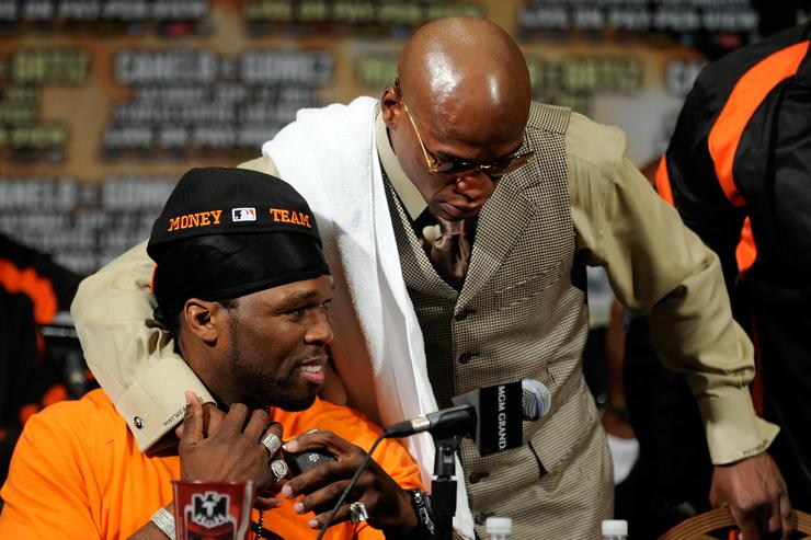 50 Cent sits at the table as he is hugged by Floyd Mayweather Jr. during the post-fight news conference after Mayweather Jr. knocks out Victor Ortiz in the WBC welterweight title fight at the MGM Grand Garden Arena on September 17, 2011 in Las Vegas, Nevada