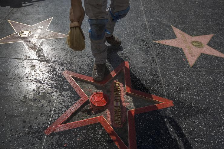 A worker sprinkles water as repairs are made on the Hollywood Walk of Fame star of Republican presidential candidate Donald Trump after it was vandalized by a protester on October 26, 2016 in Hollywood, California.