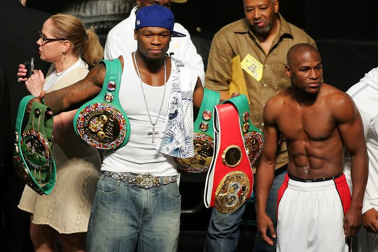 50 Cent holds up Floyd Mayweather Jr. belts at the weigh-in at the MGM Grand Garden Arena May 4, 2007 in Las Vegas, Nevada