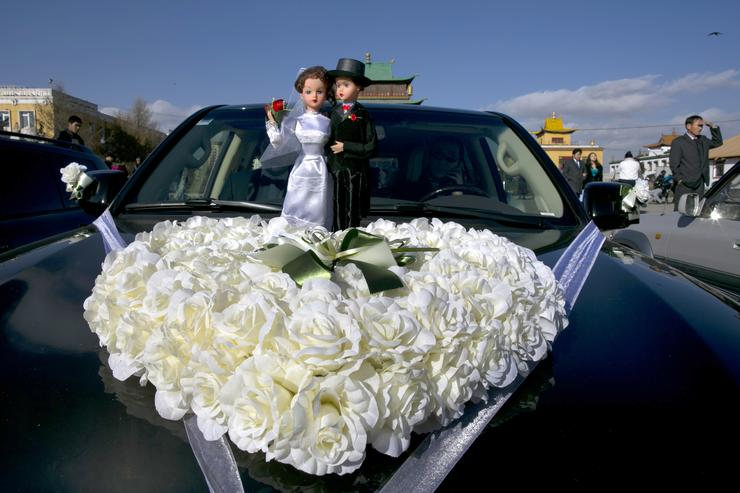A bride and groom are seen on top of a limousine at the Gandan Monastery on a special day on the Lunar calendar for wedding ceremonies October 18, 2012 Ulaanbataar, Mongolia.