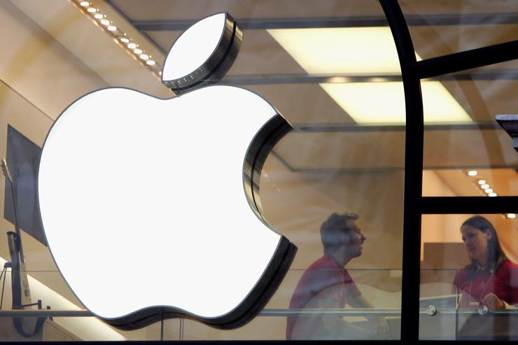 People are seen behind the Apple logo in Apple's flagship London retail store on Regent Street on December 27, 2006 in London, England