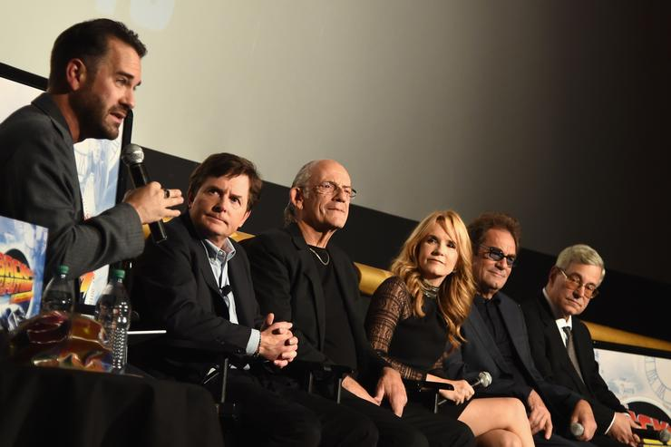 Michael J. Fox, Christopher Lloyd, Lea Thompson, Huey Lewis, and Bob Gale speak onstage with moderator Aaron Sagers during the Back to the Future reunion with fans in celebration of the Back to the Future 30th Anniversary Trilogy on Blu-ray and DVD on October 21, 2015 at AMC Loews Lincoln Square 13 in New York City.