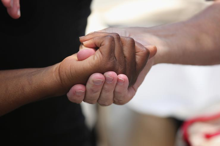 People clasp hands in prayer in front of the Emanuel African Methodist Episcopal Church on July 17, 2015 in Charleston, South Carolina. Visitors from around the nation continue to pay their respects at a makeshift shrine at the church, in a show of faith and solidarity with 'Mother Emanuel', as the church is known in Charleston.