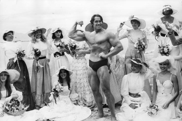 Arnold Schwarzenegger, the film actor who first became famous as Mr Universe for his magnificent physique, on Cannes beach during the Film Festival with the girls from the Folies Bergere.