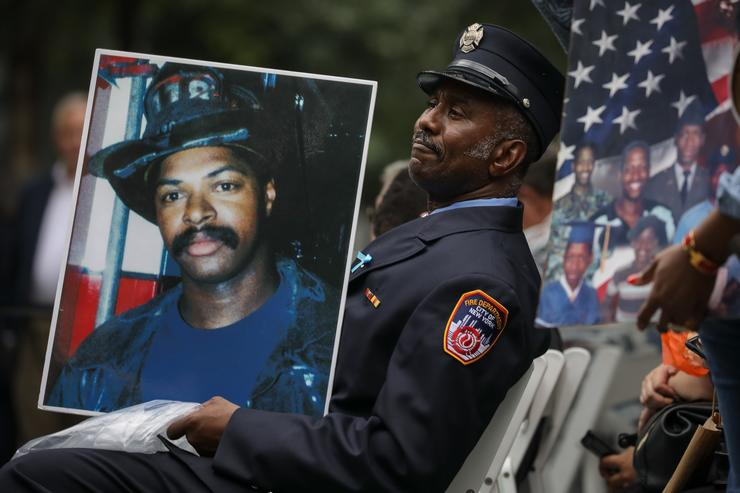 Retired New York City firefighter Bruce Stanley holds a portrait of his late friend Liam Smith Jr