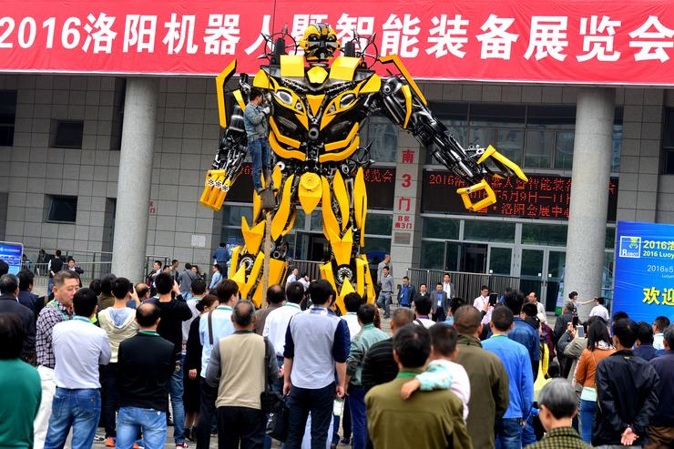 Visitors look a 'Bumblebee' transformer robot on first opening day of the China Luoyang International Robot and Intelligent Equipment Exhibition on May 9, 2016 in Luoyang, Henan Province of China. The exhibition which will last three days attracted some 200 robot and intelligent equipment manufacturers from more than 10 countries and regions.