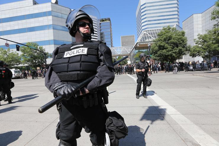Riot police stand guard as right-wing demonstrators hold a rally supporting gun rights and free speech on August 4, 2018 in Portland, Oregon.