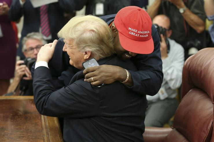 U.S. President Donald Trump hugs rapper Kanye West during a meeting in the Oval office of the White House on October 11, 2018 in Washington, DC