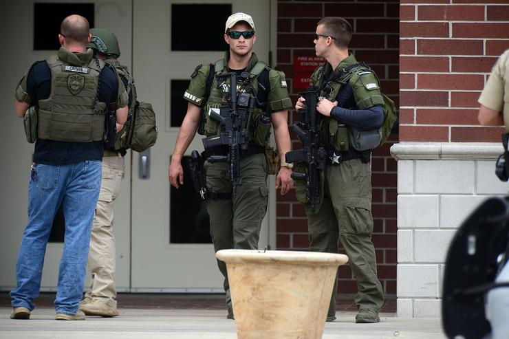 Police officers stand outside Forest High School after a school shooting on April 20, 2018 in Ocala, Florida. It was reported that a former student shot a 17-year-old male student in the ankle The shooter, whose name has not yet been released, is in custody.
