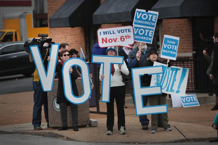 Supporters of Senator Claire McCaskill (D-MO) with signs that say vote wait for the senator to arrive for a campaign stop at The Royale bar on November 5, 2018 in St. Louis, Missouri