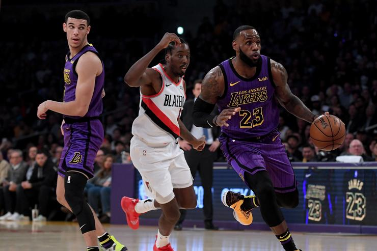 LeBron James #23 of the Los Angeles Lakers drives around a screen set by Lonzo Ball #2 as he is chased by Al-Farouq Aminu #8 of the Portland Trail Blazers during the first half at Staples Center on November 14, 2018 in Los Angeles, California.