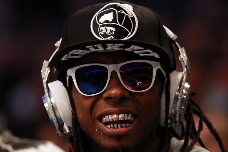 Lil' Wayne, wearing diamond studded beats headphones by Dr. Dre sits courtside during the 2012 NBA All-Star Game at the Amway Center on February 26, 2012 in Orlando, Florida