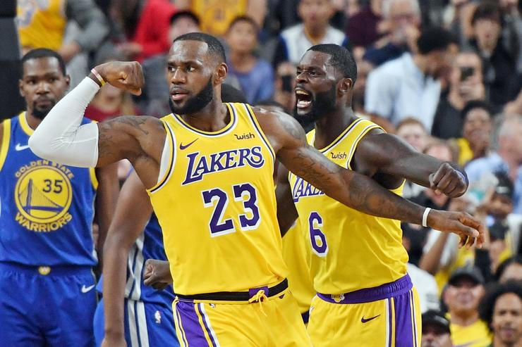 : LeBron James #23 and Lance Stephenson #6 of the Los Angeles Lakers celebrate after James made a shot against the Golden State Warriors and was fouled during their preseason game at T-Mobile Arena on October 10, 2018 in Las Vegas, Nevada.