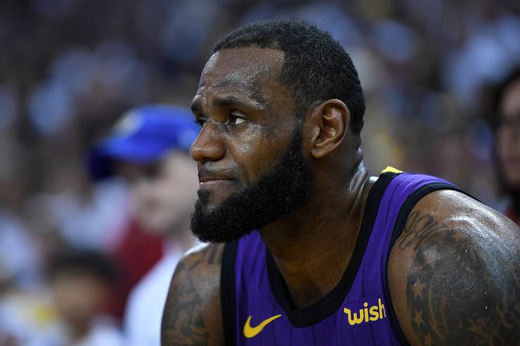 LeBron James #23 of the Los Angeles Lakers looks on from the bench after he was hurt against the Golden State Warriors during the second half of their NBA Basketball game at ORACLE Arena on December 25, 2018 in Oakland, California.
