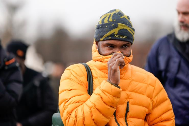 Frank Ocean wears an orange puffer jacket, a beanie hat from Arc'Teryx, outside Louis Vuitton, during Paris Fashion Week