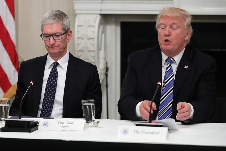 Apple CEO Tim Cook listens to U.S. President Donald Trump deliver opening remarks during a meeting of the American Technology Council in the State Dining Room of the White House