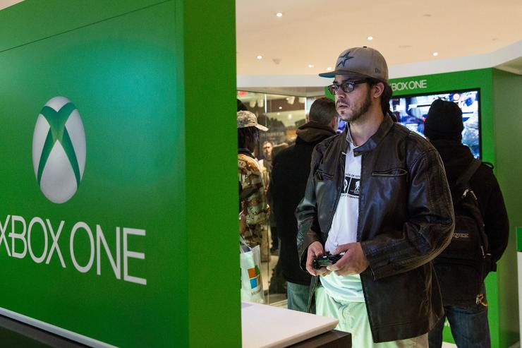 A man plays an XBox One- a new video game console and home entertainment system made by Microsoft while waiting in line to buy an XBox One from a Microsoft 'pop-up shop' at the Time Warner Center at Columbus Circle on 22 2013 in New York City